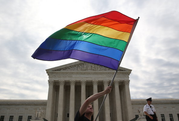 Man waving pride flag in front of Supreme Court building