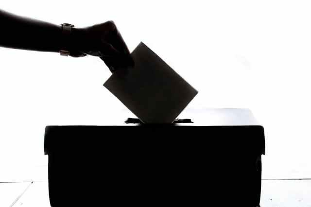 person dropping paper into ballot box